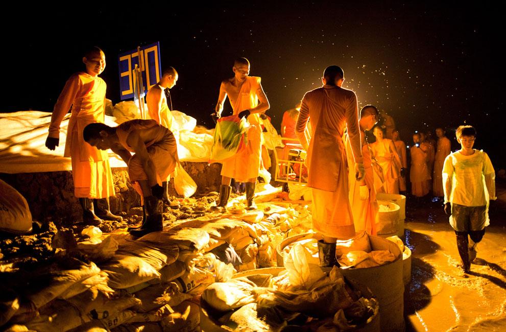 Des moines et des volontaires participent à la construction d'un mur de sable