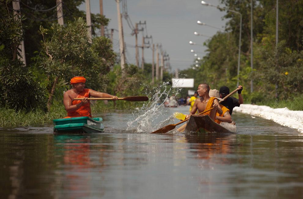 Deux moines bouddhistes s'envoient de l'eau depuis leur barque