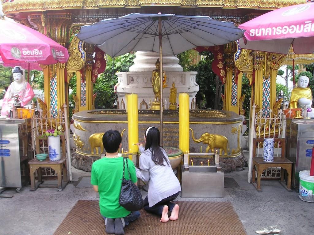 Un couple thaï se recueillant auprès d'un temple bouddhiste