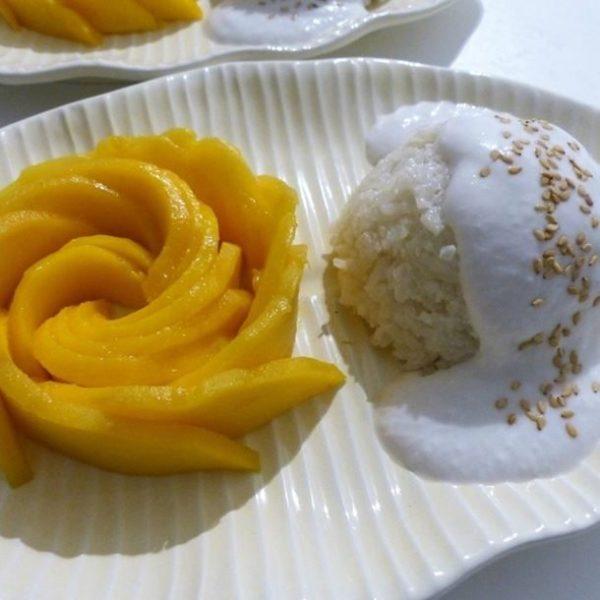 Aucun voyage en Thaïlande n'est complet sans un goût, ou une indulgence, pour être honnête, du khao niao mamuang ou riz gluant à la mangue. C'est l'un des plats de rue sucrés les plus populaires du pays, un favori des habitants et des touristes. Pour les non-initiés, la combinaison de riz et de mangue dans un plat ne semble pas délectable, mais les Thaïlandais ont réussi à marier ces deux ingrédients dans une délicieuse collation sucrée. Du riz gluant moelleux est servi avec des joues charnues de mangue mûre, puis recouvert d'un riche sirop de crème de noix de coco. Essayons d'en savoir plus sur ce célèbre dessert thaïlandais. Khao niao mamuang : c'est quoi exactement ? Si vous deviez limiter votre consommation de desserts à un seul plat, vous devriez certainement opter pour le khao niao mamuang, ne serait-ce que pour les mangues thaïlandaises. Ces dernières sont réputées pour être parmi les mangues les plus sucrées du monde. Ce riz au lait thaï traditionnel, est une des meilleures façons de terminer n'importe quel repas thaïlandais. Le plat est préparé avec du riz gluant qui est d'abord cuit à la vapeur, puis aspergé de lait de coco sucré. Enfin, le riz est servi accompagné de tranches de mangue fraîche. Ce dessert simple est incroyablement populaire et on le trouve dans pratiquement tous les restaurants de Thaïlande. Il se mange pendant les mois d'été de la saison des mangues (avril - mai) avec une cuillère ou parfois avec les mains. Vous pouvez également le déguster n'importe où, car on le trouve couramment dans la cuisine de rue. Le riz gluant à la noix de coco et à la mangue est un dessert populaire dans la région d'Indochine en Asie du Sud-est, qui comprend la Thaïlande, le Cambodge, le Laos et le Viêtnam. Il est généralement servi légèrement chaud ou à température ambiante. Certains endroits le servent avec une petite tasse de sauce à la noix de coco à verser sur le riz gluant, tandis que d'autres le servent avec la sauce déjà versée pour vous. Les ingrédient