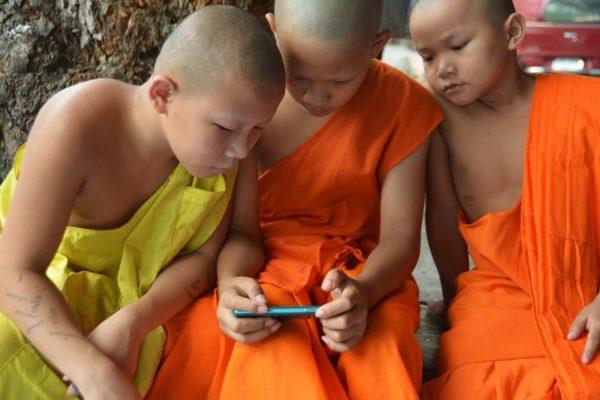 Petits moines jouant à un jeu sur mobile